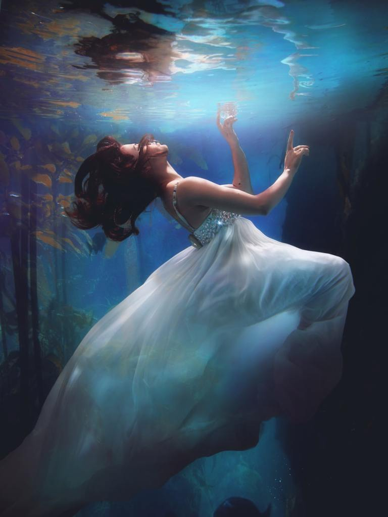 underwater photography of woman wearing white dress